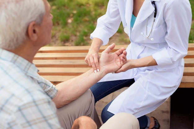 Doctora mide el pulso de un paciente anciano.
