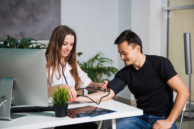 Doctora midiendo la presión arterial del paciente en el tonómetro antiguo en la clínica. concepto de salud y médico