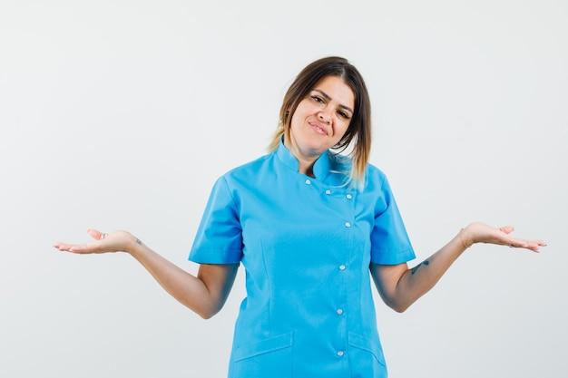 Doctora mostrando gesto de impotencia en uniforme azul y mirando positivo