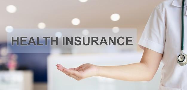 Doctora mostrando texto de seguro médico con desenfoque de fondo de habitación de hospital concepto de salud