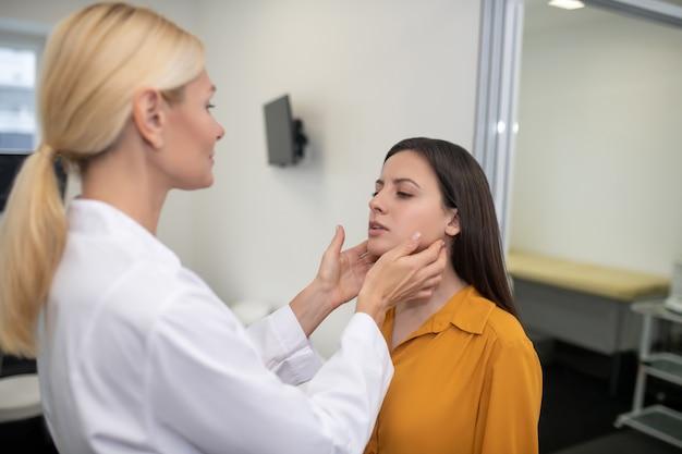 Doctora palpando los ganglios linfáticos del paciente de pie frente a ella