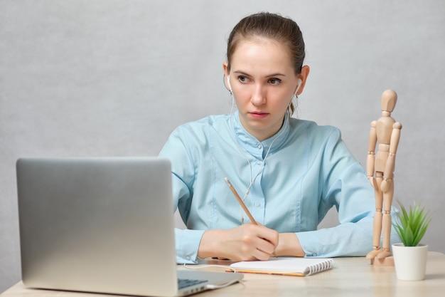 Doctora pasa a grabar en línea en una computadora portátil y toma notas.