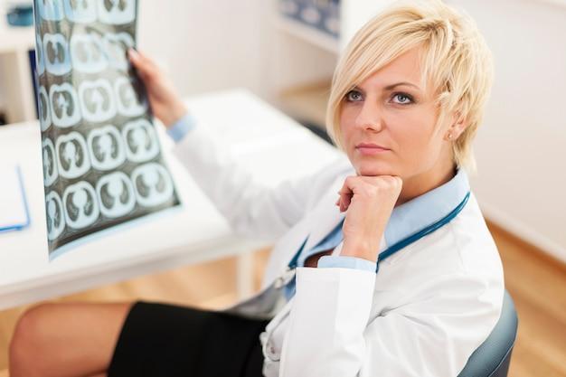 Doctora pensativa con imagen de rayos x