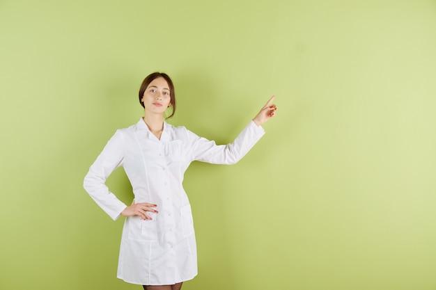 Doctora de piel blanca, doctora con bata blanca, señala con la mano algo
