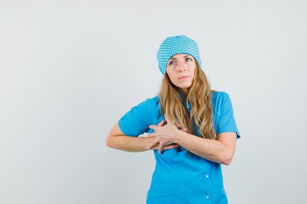 Doctora que tiene dolor en el pecho en uniforme azul y parece incómodo