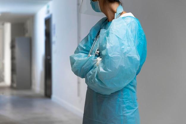Doctora en ropa protectora mirando a otro lado en el pasillo