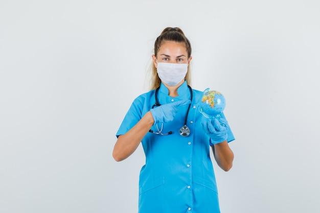 Doctora, señalar con el dedo en el globo del mundo en uniforme azul