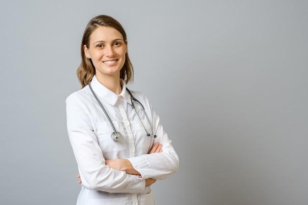 Doctora sonriente en bata de laboratorio con los brazos cruzados
