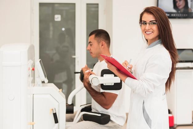 Doctora sonriente que controla la condición del paciente