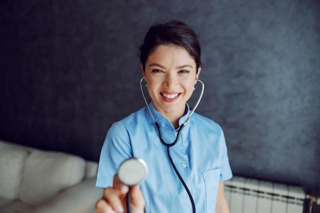 Doctora sonriente sosteniendo un estetoscopio hacia la cámara como si estuviera examinando los pulmones