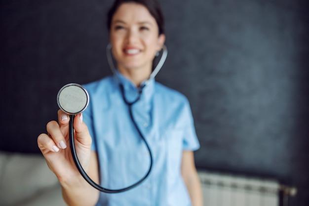 Doctora sonriente sosteniendo un estetoscopio hacia el frente como si estuviera examinando los pulmones