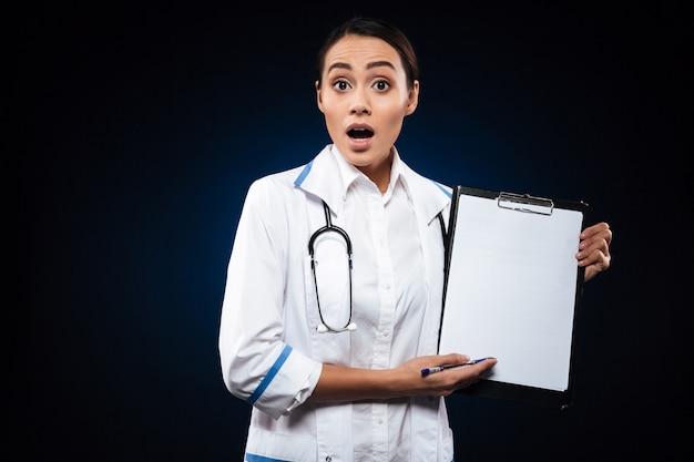 Doctora sorprendida en bata médica blanca mostrando portapapeles en blanco aislado