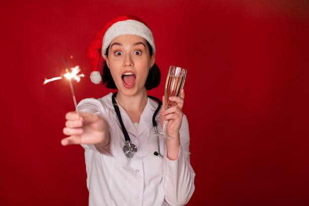 Doctora sosteniendo una copa de champán y quemando bengalas en sus manos