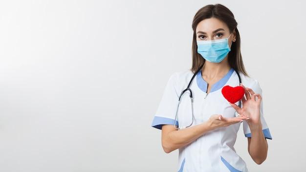 Doctora sosteniendo un corazón de felpa con espacio de copia