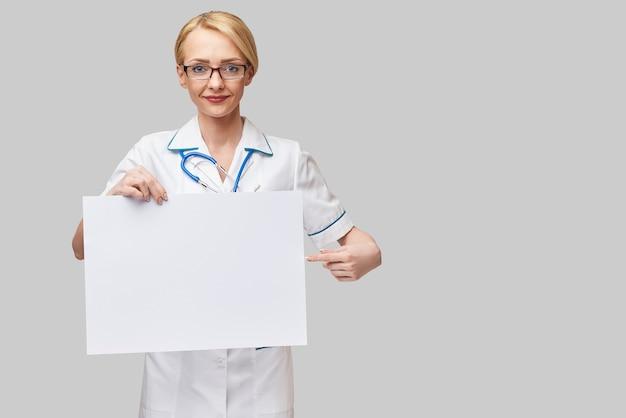 Doctora sosteniendo una hoja de papel en blanco o un cartel