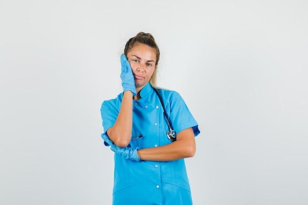 Doctora sosteniendo la palma en la mejilla en uniforme azul, guantes y mirando pensativo.