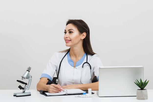 Doctora sosteniendo una pluma y mirando a otro lado