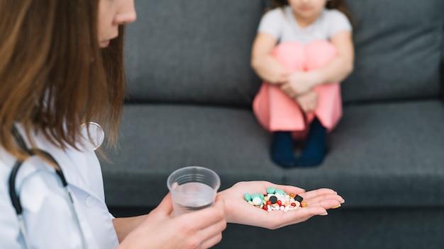 Doctora sosteniendo un vaso de agua y medicinas en la mano de pie delante de una niña enferma sentada en el sofá