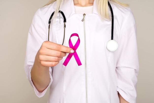Doctora sostiene la cinta rosada, día internacional del cáncer de mama, 7 de octubre