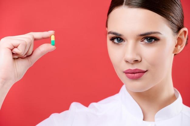 Doctora sostiene una píldora. enfermera muestra una cápsula con medicina.