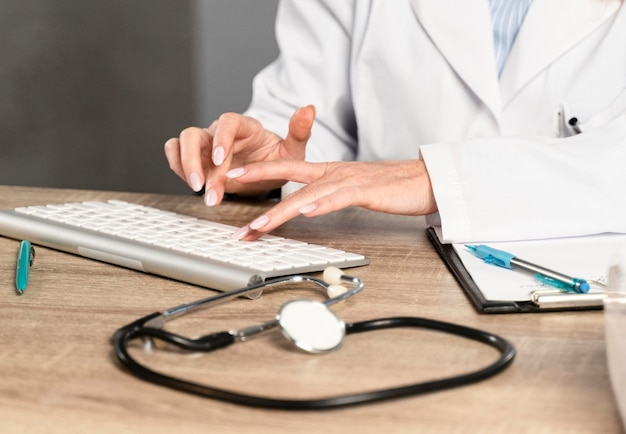 Doctora en su escritorio escribiendo en el teclado