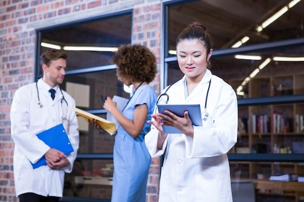 Doctora con tableta digital cerca de la biblioteca y colegas de pie detrás y discutiendo