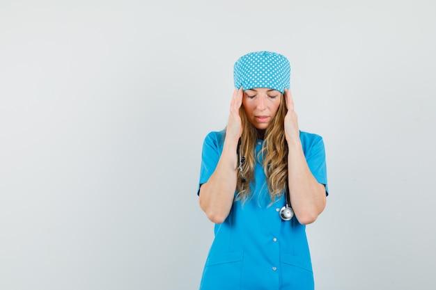 Doctora tocando las sienes, con dolor de cabeza en uniforme azul y con aspecto fatigado