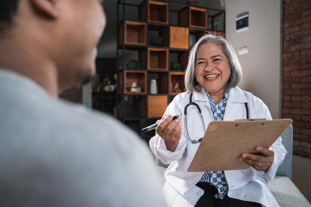 La doctora toma notas con el portapapeles cuando le pregunta a su paciente