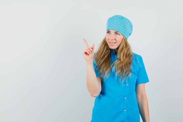 Doctora en uniforme azul apuntando hacia arriba y mirando alegre