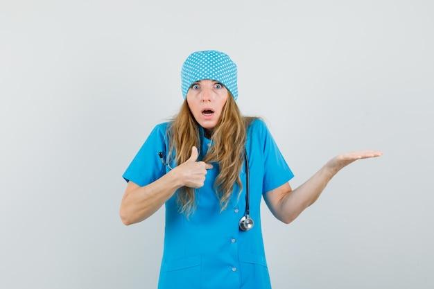 Doctora en uniforme azul gesticulando para preguntar