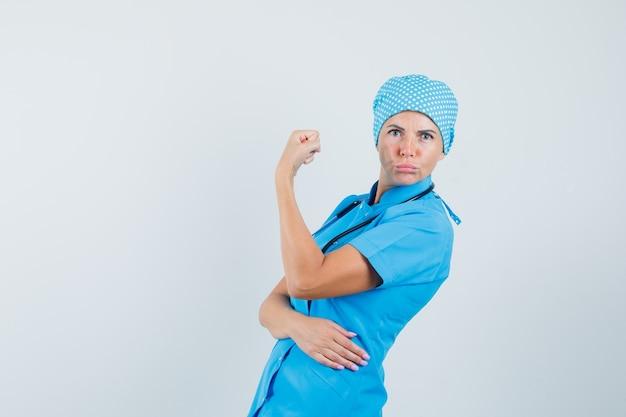 Doctora en uniforme azul mostrando los músculos del brazo y mirando confiado.