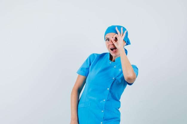 Doctora en uniforme azul mostrando signo ok en el ojo y mirando asombrado, vista frontal.