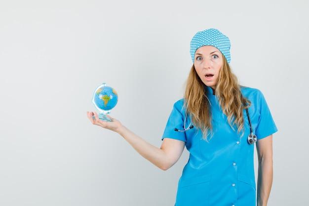 Doctora en uniforme azul sosteniendo globo terráqueo y mirando ansioso