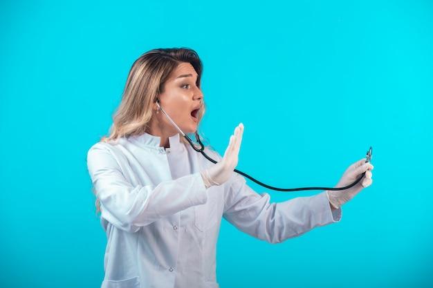 Doctora en uniforme blanco comprobando con estetoscopio.