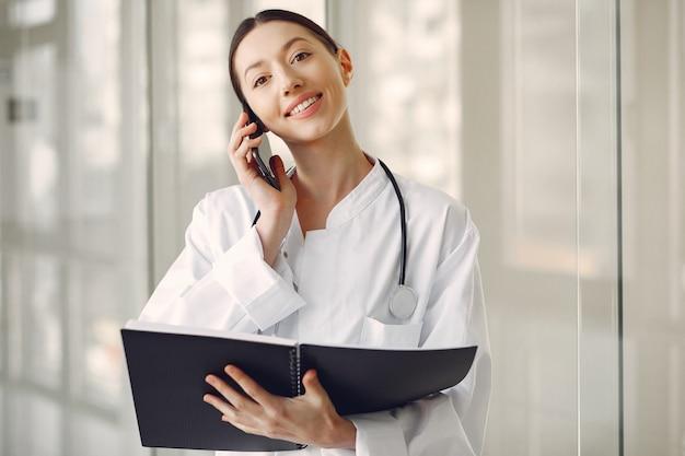 Doctora en uniforme blanco de pie en una sala