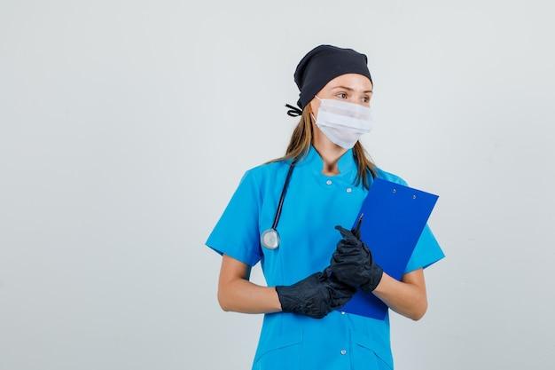 Doctora en uniforme, guantes, máscara mirando a un lado con portapapeles y lápiz