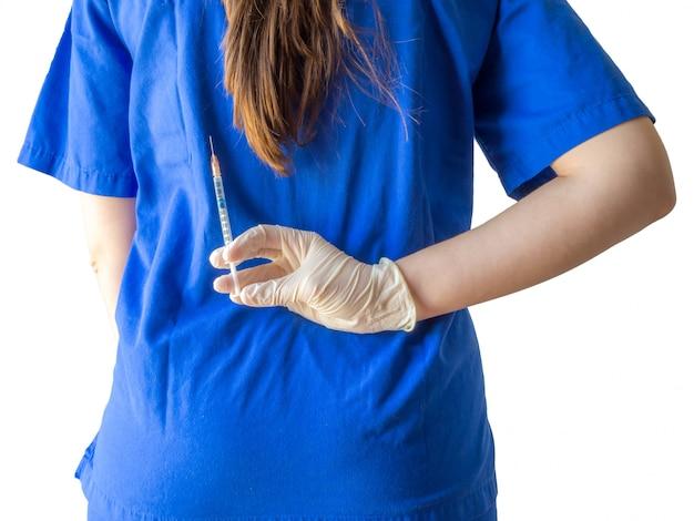 Doctora en uniforme médico azul con guantes esterilizados sosteniendo una jeringa detrás de su espalda