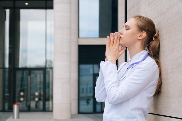 Una doctora en uniforme tiene estrés y oración durante un brote