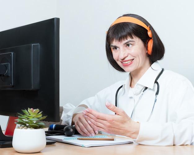 Una doctora usa un auricular hace una videollamada en línea, discute, gestos