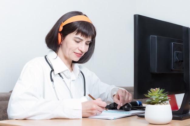 Una doctora usa un auricular hace una videollamada en línea con un paciente, firma un documento en su oficina