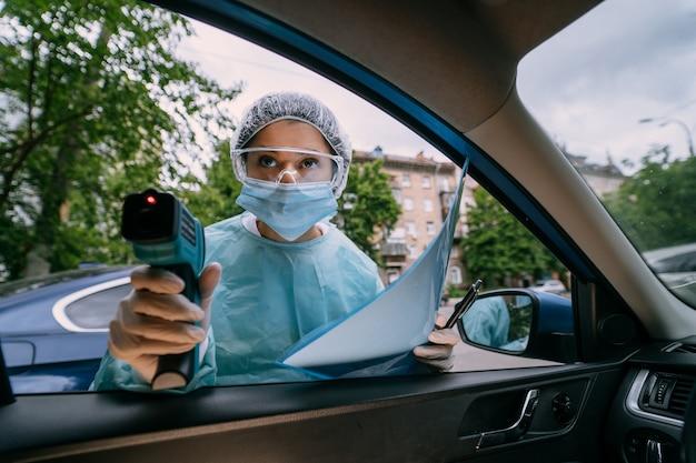 La doctora usa una pistola de termómetro infrarrojo para la frente para verificar la temperatura corporal. para los síntomas del virus covid-19. mujer con la bata de aislamiento o trajes de protección y mascarillas quirúrgicas al aire libre.