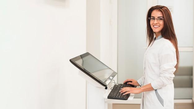 Doctora usando la computadora y mirando al fotógrafo
