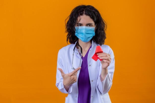 Doctora vistiendo bata blanca con estetoscopio en máscara protectora médica sosteniendo una cinta roja un símbolo de la lucha contra el sida apuntando con el dedo de pie en naranja aislada