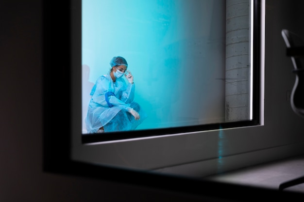 Doctora vistiendo ropa protectora detrás de la ventana