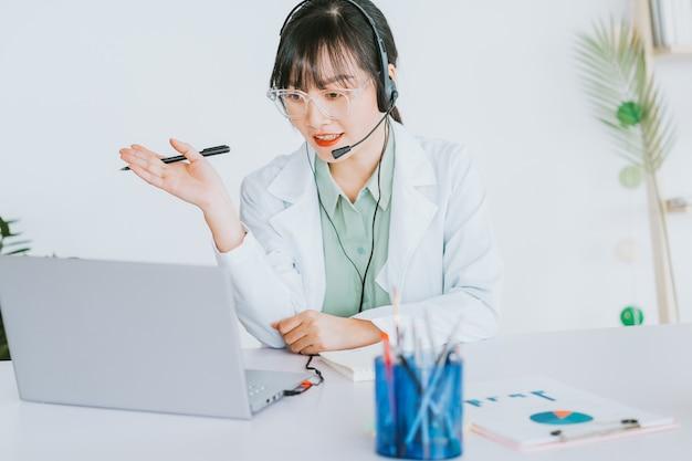 Las doctoras asiáticas están examinando a los pacientes de forma remota, los doctores ahora pueden usar software de videollamadas en computadoras para buscar clientes en línea.