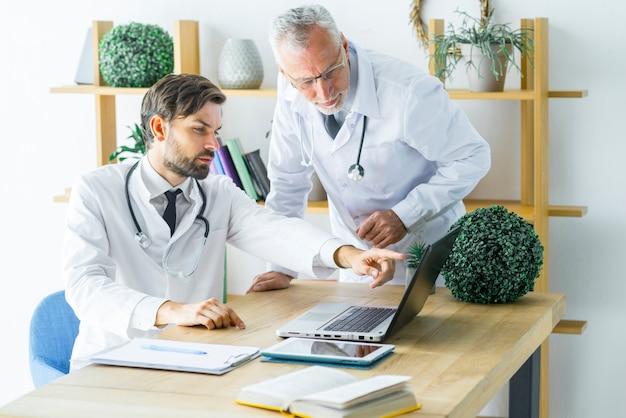 Doctores discutiendo datos en la computadora portátil