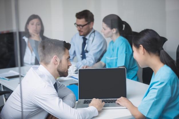 Doctores discutiendo sobre laptop en reunión