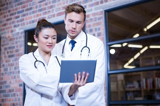 Doctores discutiendo sobre tableta digital cerca de la biblioteca en el hospital