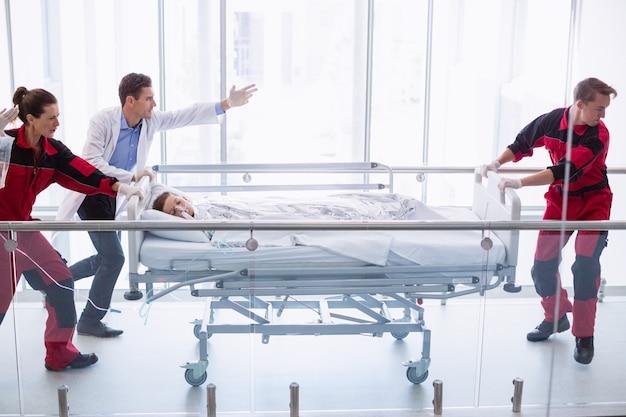 Doctores empujando la camilla de emergencia en el pasillo