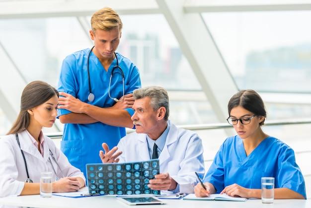 Los doctores están sentados a la mesa y discutiendo algo.